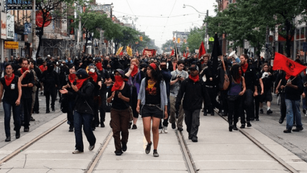 Harjap Grewal & Harsha Walia providing cover for the Black Bloc during the G20