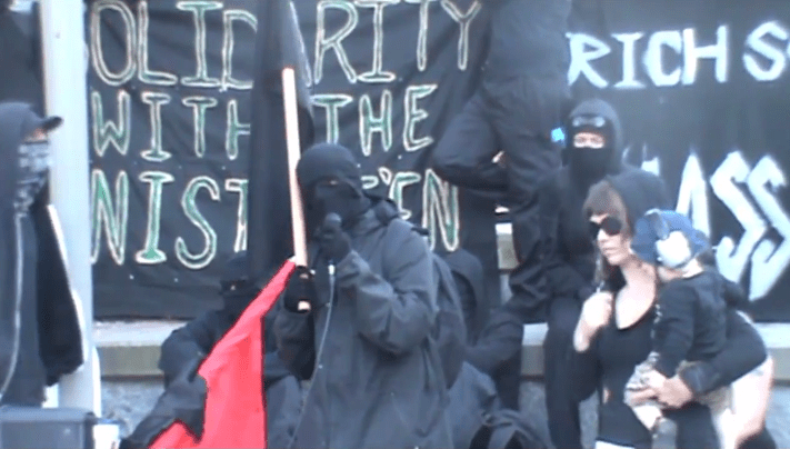 Masked Black Bloc anarchists give a speech at the cenotaph