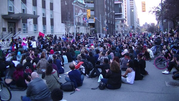 Protesters sit-down blocking University Ave in front of the US Consulate