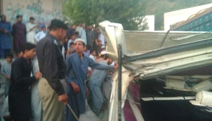 Police officials inspect the ill-fated passenger van at the site of the accident. Photo: Geo News