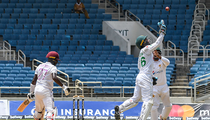 Mohammad Rizwan (R) of Pakistan celebrates taking the catch to dismiss Jermaine Blackwood (L) of West Indies during the 5th and final day of the 2nd Test between West Indies and Pakistan at Sabina Park, Kingston, Jamaica, on August 24, 2021. — AFP
