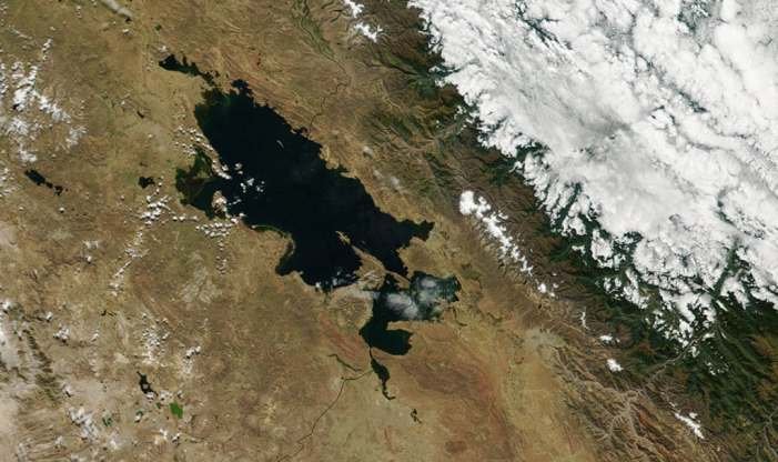 A satellite image showing Lake Titicaca, which straddles the border of Peru and Bolivia with the Andes Mountains to the top right.  Source: NASA