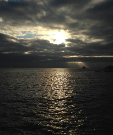 A column of sunlight falls on a minor Galapagos island