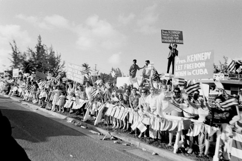 """Crowd gathers along roadside in San Juan, Puerto Rico, for the arrival of President John F. Kennedy and First Lady Jacqueline Kennedy."""