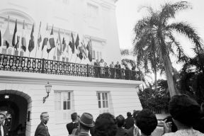 """President John F. Kennedy and First Lady Jacqueline Kennedy stand on the balcony at the Governor's mansion (La Fortaleza) upon their arrival in San Juan, Puerto Rico. Also pictured are Governor of Puerto Rico Luis Muñoz Marín and First Lady of Puerto Rico Inés Mendoza."""