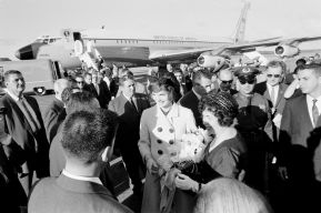 """First Lady Jacqueline Kennedy and First Lady of Puerto Rico Inés Mendoza (right) visit with those gathered at Isla Verde International Airport to welcome President John F. Kennedy and Mrs. Kennedy upon their arrival. San Juan, Puerto Rico."""