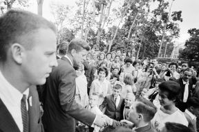 """President John F. Kennedy upon his arrival at the Governor's mansion (La Fortaleza) in San Juan, Puerto Rico; students from Latin American countries studying in Puerto Rico greeted the President. White House Secret Service agent, Ed Tucker, stands at left in foreground."""