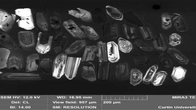 Zircon crystals examined with an electron microscope. The brighter and more concentrically zoned crystals with nice straight edges are the volcanic zircons. Credit: Milo Barham