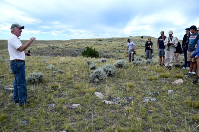 Bob Haseman talks about a buffalo jump in the Toston Valley. He is standing by one of the many tepee rings associated with the jump site.