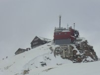 Der Gipfel des Sonnblick (3.108m) ist frei, aber es sind wieder Wolken aufgezogen. Voraus liegen die Wetterstation und das Zittelhaus