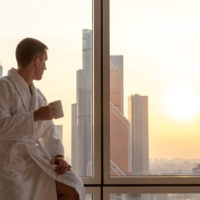 55215473 - focus on laptop computer with copy space blank screen on the bed. young businessman sitting on window with cup of coffee looking at sunset city scenery