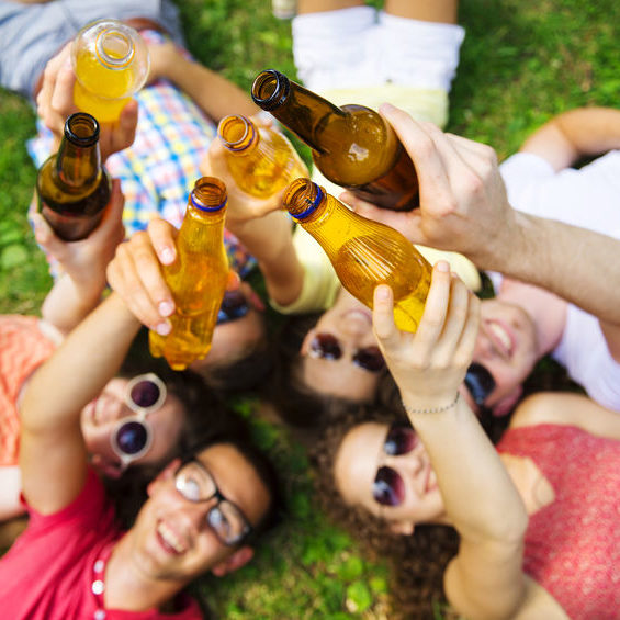 31523683 - group of young people having fun in park, lying on the grass with drinks