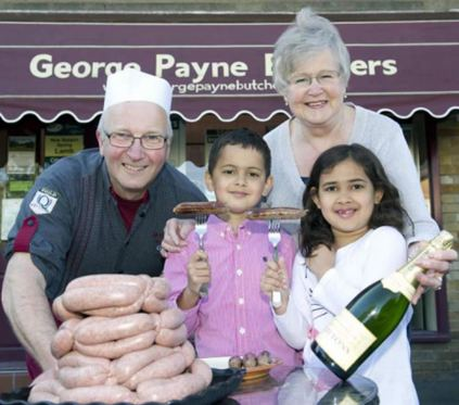 Daniel Bansal, accompanied by his sister and grandma, is pictured with butcher George Payne outside the Brunton Park shop with his Diamond Jubilee sausage that scooped a gold award in the national product evaluation event.