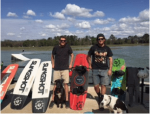 Two young men in t-shirts and shorts stand next to four large wakeboards. A large lake is behind them, with trees in the far background. A cute dog sits at the feet of one man, looking at the camera.
