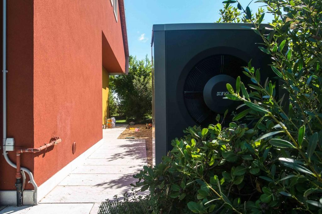 vista esterna della pompa di calore aria-acqua IVT AirX 90 villetta a schiera in provincia di Verona, integrata nel verde del giardino