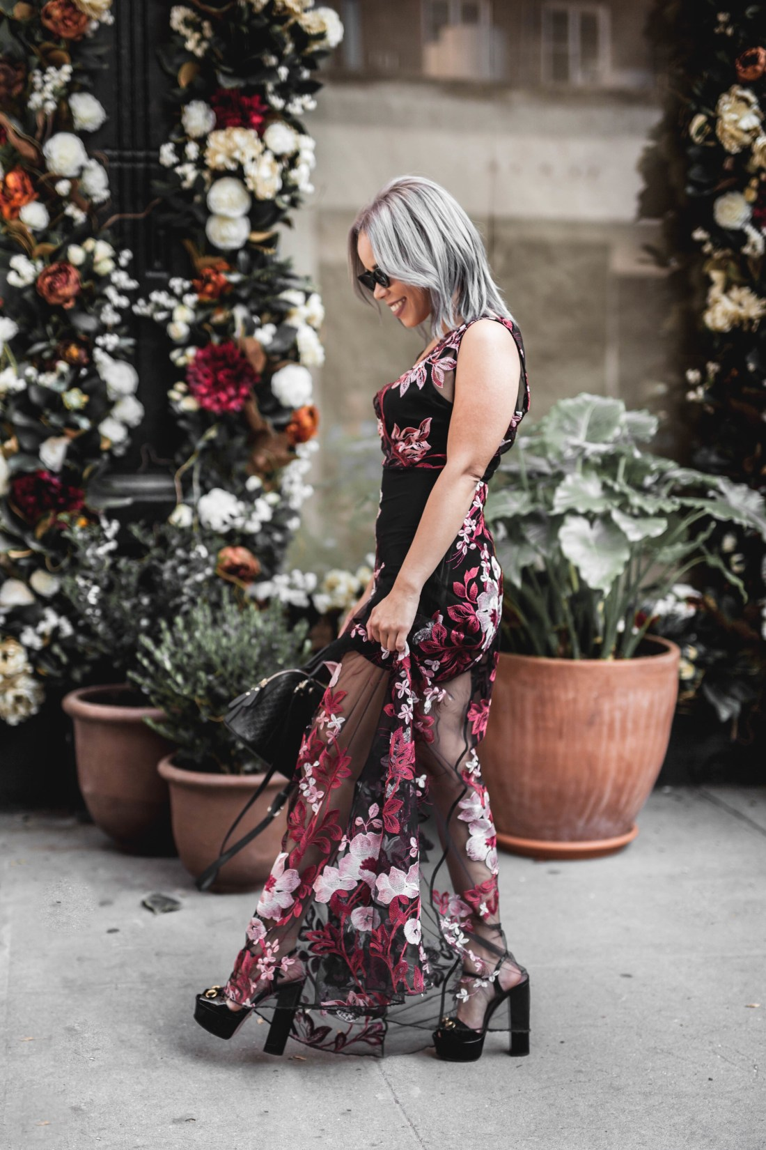 A girl wearing a long floral dress for a fashion street style shoot