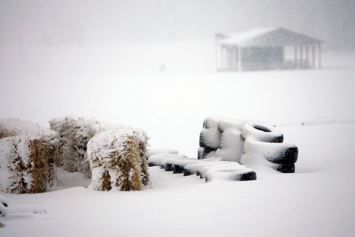 Hay bails and tires sit stacked and snow-covered at the bottom of a popular sled hill in Memorial Park. (C-T photo Max Gersh)