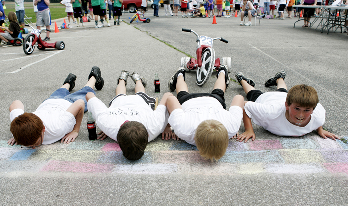 In this May 26, 2010 photo, members of the the No. 23 Dr. Pepper team and winners of the race, from left, Jordan Rhodus, Grant Jessup and Travis Isaacs kiss the chalk-drawn bricks at the Titan 500 while teammate Corbin Pew lifts his head at the end of the Big Wheel tricycle race at Tri Elementary School in Straughn, Ind. (AP Photo/The Courier-Times, Max Gersh) ©2010