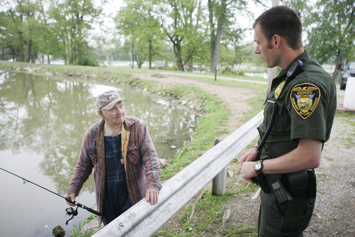 Indiana Conservation Officer Zach Walker, right, talks with New Castle resident Wayman Hoots Wednesday, May 19 in Memorial Park. Walker was checking on Hoots' catch for the day to make sure he was within the legal limit. (C-T photo Max Gersh) ©2010