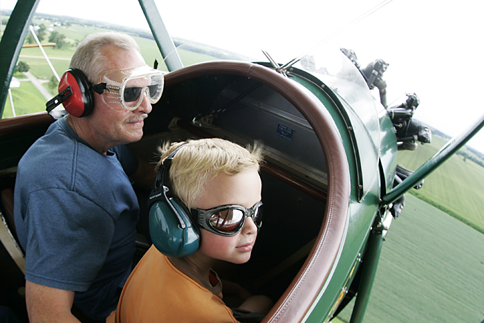 Logan Drook, 6, looks out at Henry County farm land Tuesday afternoon while taking a biplane ride with his grandpa, Roger Peckinpaugh. (C-T photo Max Gersh) ©2010