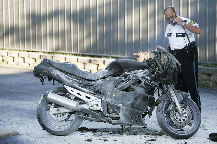 Vaughn Reid Jr. looks down at a motorcycle that had caught on fire Thursday night shortly after the bike had been extinguished. The motorcycle was supposed to be sold later the same evening.(C-T photo Max Gersh) ©2010