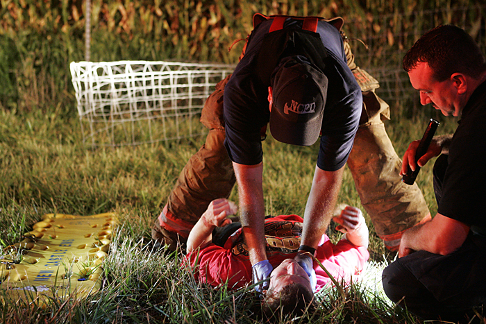 Emergency responders check Justin Ryan Pierce, 19, of Mount Summit, for injuries late Wednesday night after he crashed a 1987 Mercedes Benz into a cornfield near the intersection of Road 300S and Ind. 103. (C-T photo Max Gersh) ©2010