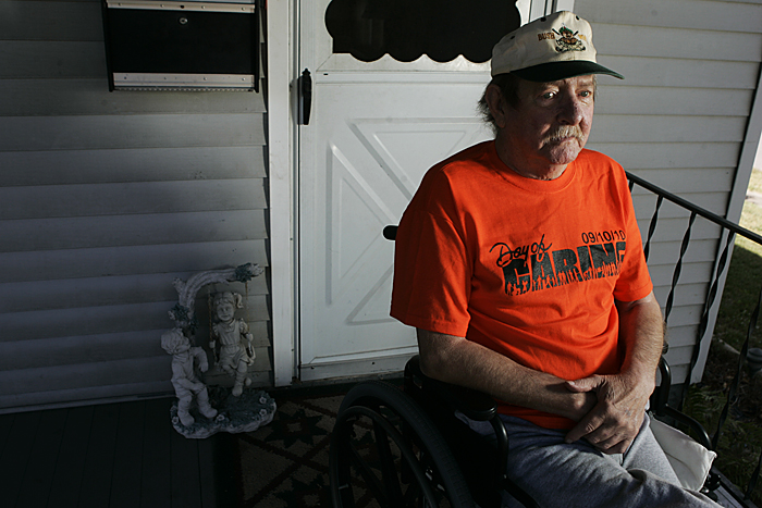 Bud Bush, who frequently participates in the Henry County Day of Caring, sits on his front porch Thursday afternoon next to a new ramp that was built for him by volunteers. (C-T photo Max Gersh) ©2010