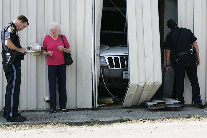 Opal Dixon talks with Sgt. Adrian Darwin after her Jeep went through a building Monday afternoon while backing down her driveway. (C-T photo Max Gersh) ©2010