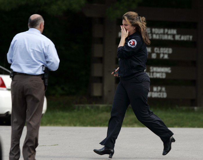 MAX GERSH | ROCKFORD REGISTER STAR Winnebago County dispatcher Tracy Wilson runs from her vehicle into a waiting police car after her 17-year-old son, Mitchel Krause, was pulled from the water Tuesday, June 14, 2011, at a boat dock in Rock Cut State Park in Loves Park, Ill. ©2011
