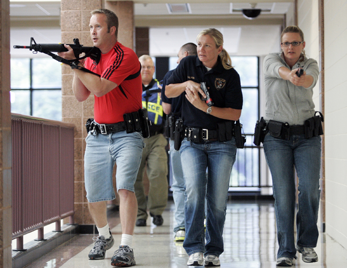 MAX GERSH | ROCKFORD REGISTER STAR Ryan Fulton (from left) of the Cherry Valley Police Department, Ashley Calhoun of the Rockford Police Department, and Adrienne Horn of the Rock Valley College Police Department clear a hallway Wednesday, Aug. 10, 2011, during rapid deployment to an active shooter training at Harlem High School in Machesney Park. ©2011