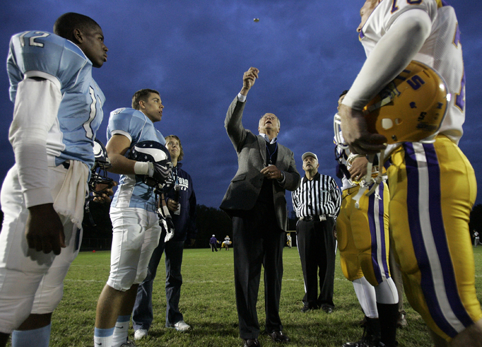 MAX GERSH | ROCKFORD REGISTER STAR Rockford School Board President Harmon Mitchell tosses a Ronald Reagan commemorative coin Friday, Sept. 23, 2011, before a game against Belvidere at Guilford High School in Rockford. © 2011