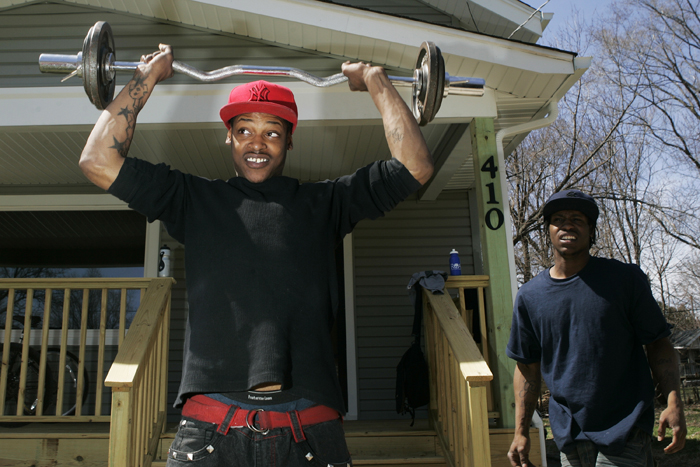 "MAX GERSH | ROCKFORD REGISTER STAR Elijah Chandler, right, watches his brother, Emmanuel Chandler, lift weights in Edvon Macklin's (not pictured) driveway Tuesday, April 12, 2011, on Oakley Avenue near Andrews Street in Rockford. Macklin said he tries to be a role model for younger men in the neighborhood. ""From just coming outside with a curl bar, people wanted to come and join,"" he said. ""You have to get out here and physically do something to make a change."" ©2011"