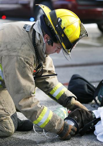 firefighter giving dog oxygen