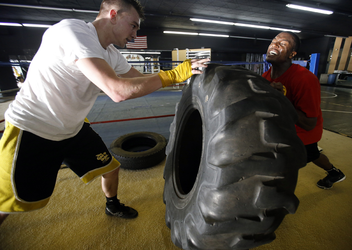 "Ryan Newman (left), 20, and Joshua Patterson, 24, push a tire back and forth during a ""standing pushup"" exercise Tuesday, April 30, 2013, at Fight College on North Main Street in Rockford. MAX GERSH/ROCKFORD REGISTER STAR ©2013"