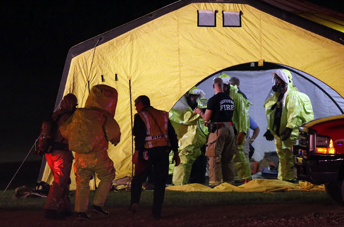 A hazardous materials team member from MABAS Division 8 is walked back to a changing tent Tuesday, June 4, 2013, at the Winnebago County Farm Bureau in Rockford. MAX GERSH/ROCKFORD REGISTER STAR ©2013