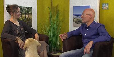 Antje Tittelmeier im Gespräch mit Dr. Ruediger Dahlke. Studiohund Pelle sieht zu.