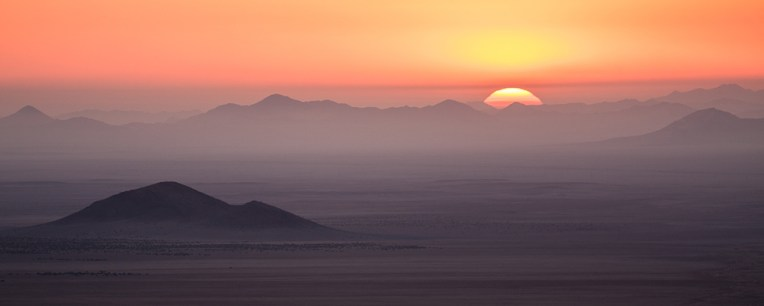 Sunset photos are a dime a dozen, but sometimes one may get something special. Here the sun is setting over the mountains outside Lüderitz, Namibia. The mountains can be seen from nearly 100km away. There is so much air in the way that the image brings to mind a Chinese silk painting. Local contrast adjustments were made, as well as a crop to wide format. - By Florian Breuer, Stellenbosch Canon 40D, Canon 70-200mm f/4, ISO 100, f/4, 1/100 sec