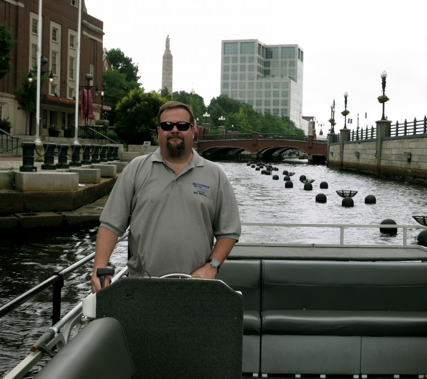 Captain Tom McGinn at the helm of his 28 ft. pontoon river boat, Providence, RI
