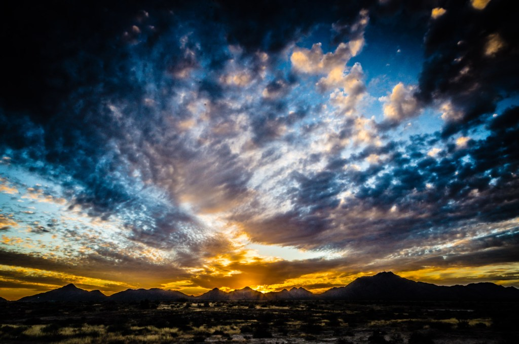 A breathtaking sunset over open roadside land in Arizona.