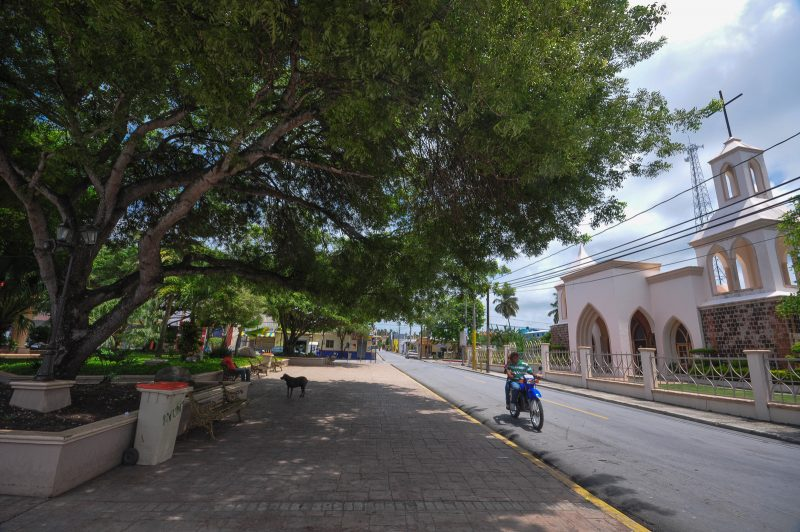 Motorcyclists passes the church and a dog in the town square in Cabrera, Dominican Republic.