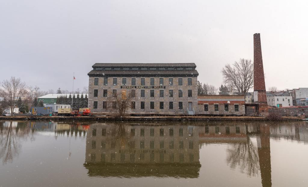 Waterfront view of Seneca Knitting Mill, now The Center for Great Women, during snow shower.