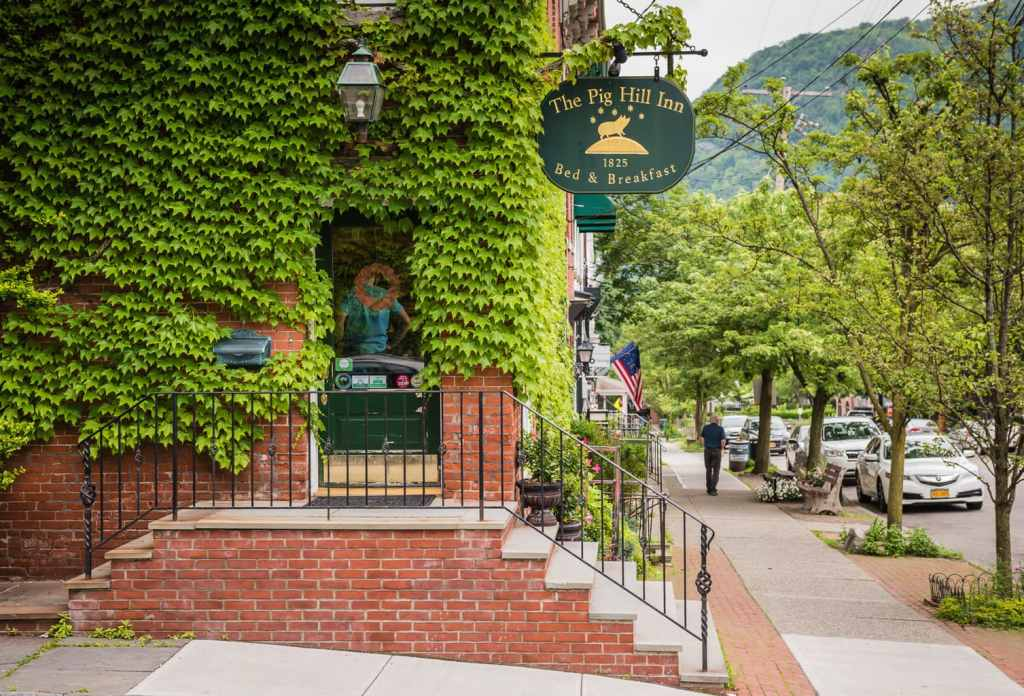 Ivy covered historic building of Pig Hill Inn on street corner in Cold Spring, New York.