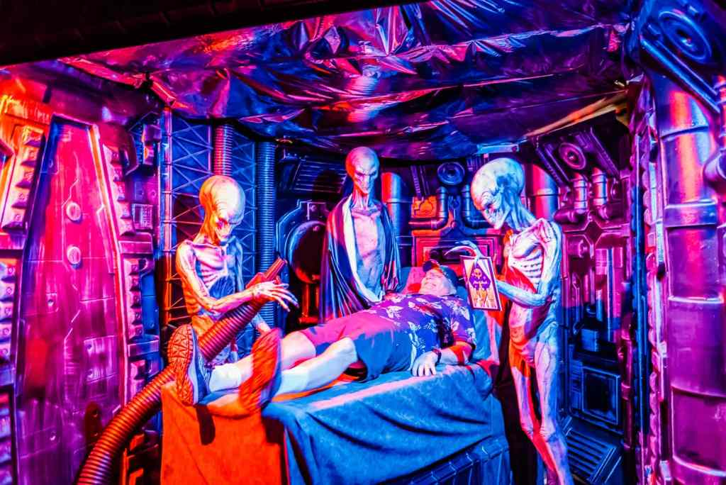 Tourist lies on examining table where he is surrounded by aliens at UFO Fair pop-up museum.