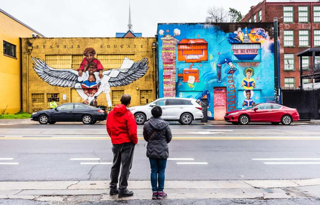 African American couple views mural about education and Black History in Atlanta GA.