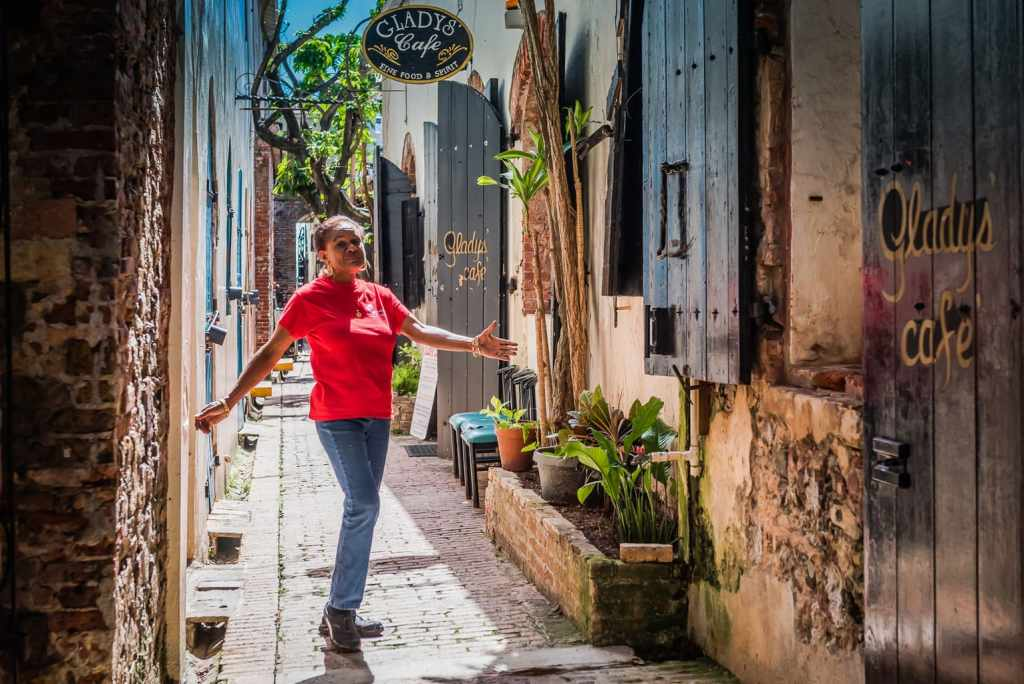 Gladys, owner of Gladys Cafe, poses in the alley where her restaurant is located.