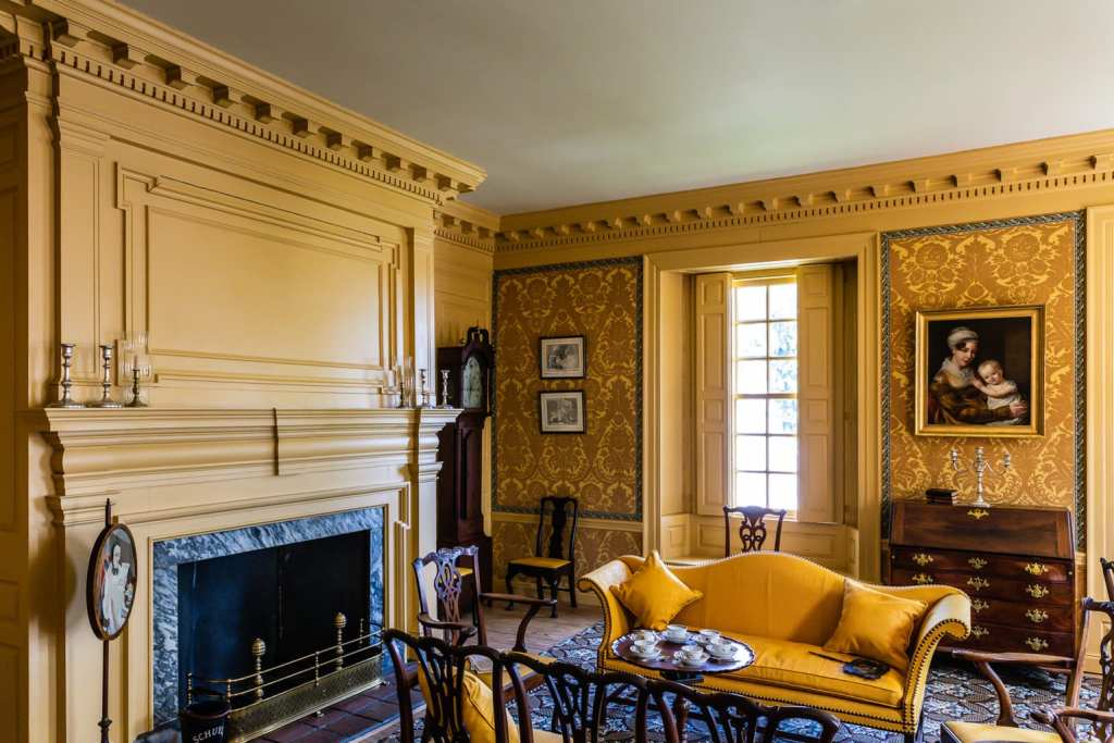 Schuyler Mansion interior room with yellow decor and flock wallpaper.