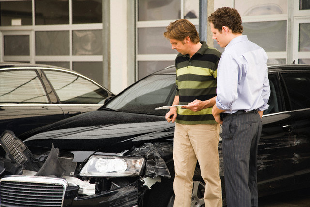 TAuto Claims Adjuster Assessing Damage to a vehicle  Get Insurance Claim Help