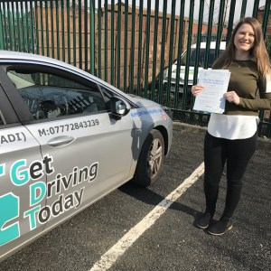 Justyna displays her pass certificate after passing her driving test in Bury