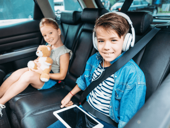 Kids in the car with a boy wearing headphones and using a tablet.