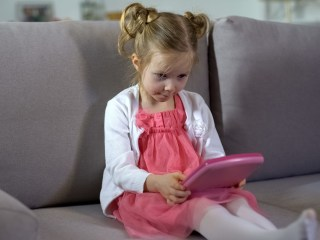 Little girl playing with a learning app.